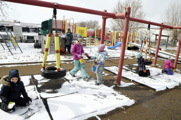 Children playing on a swing set with snow on the ground.