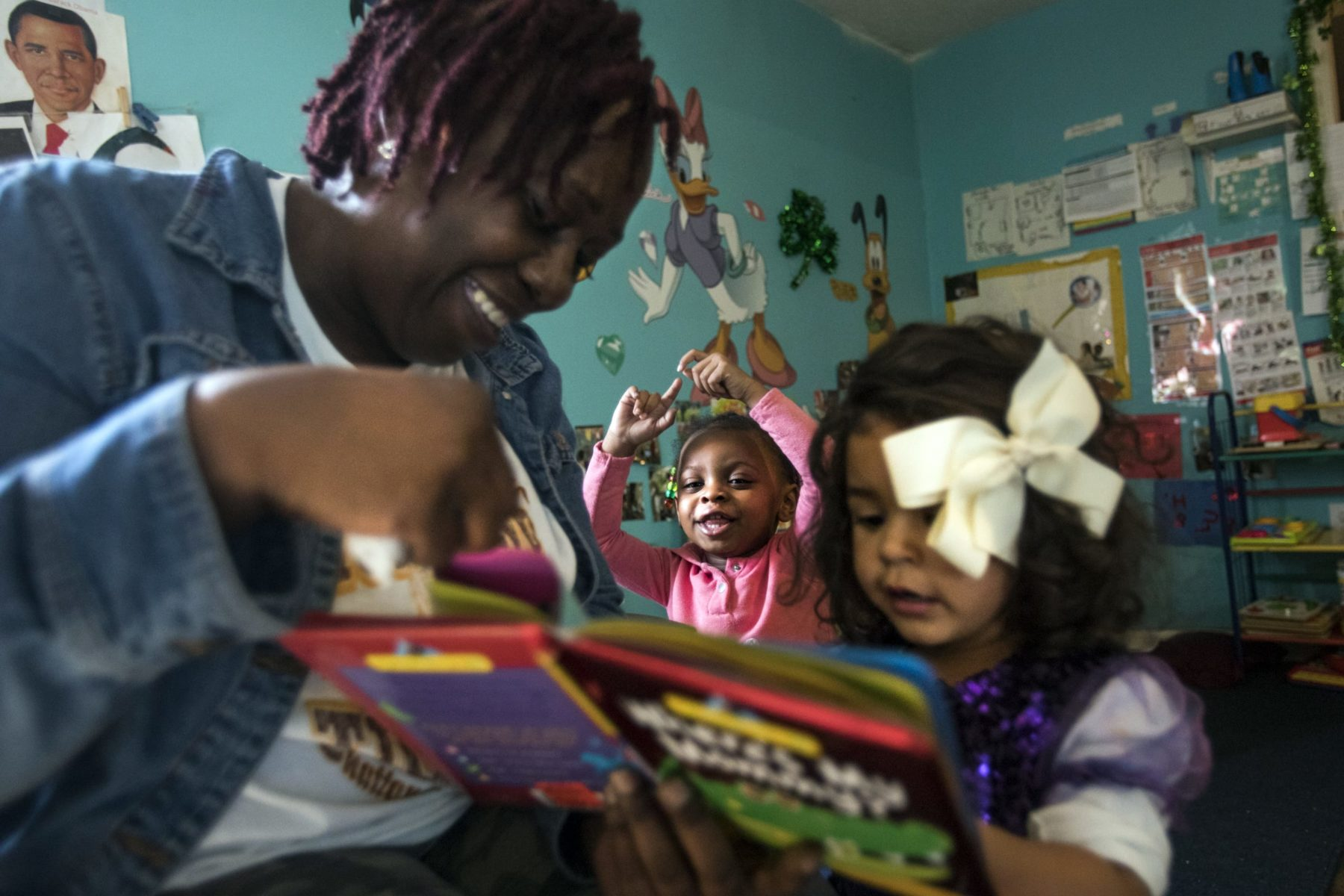 A woman reads a book to two small children.
