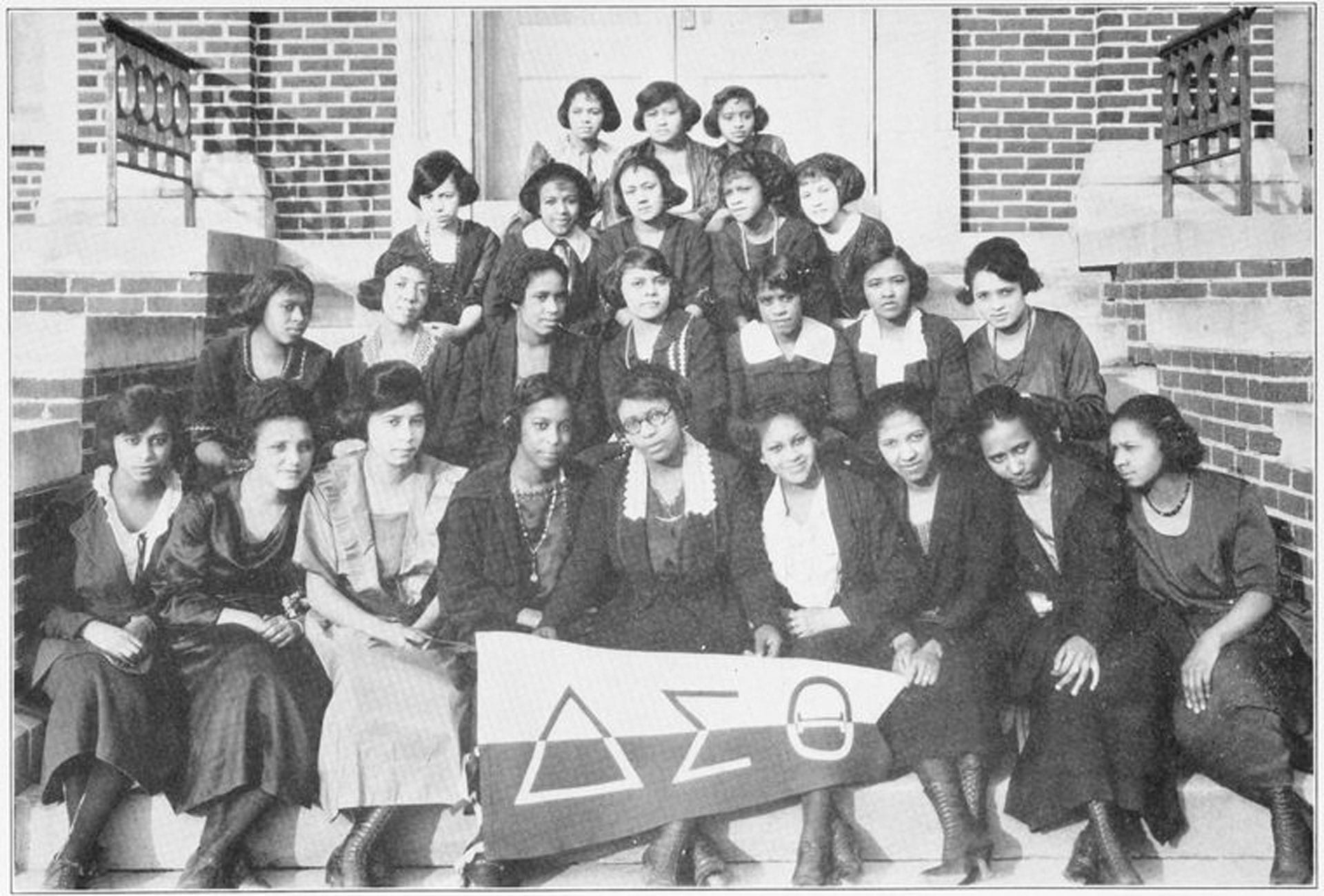 A group of women gathered on steps with a Delta Sigma Theta banner.