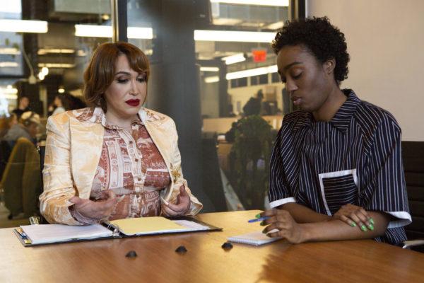 A transfeminine executive meeting with a non-binary employee