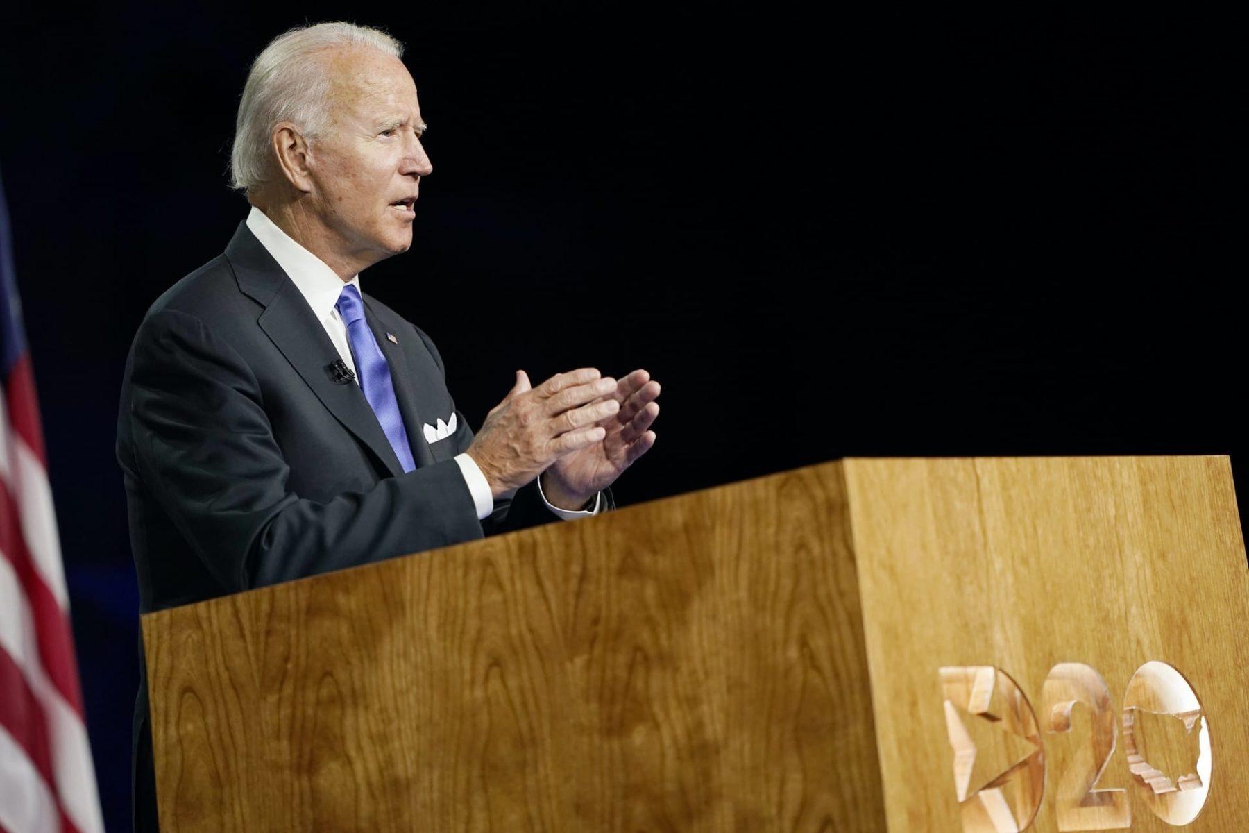 Joe Biden stands at a lecturn.