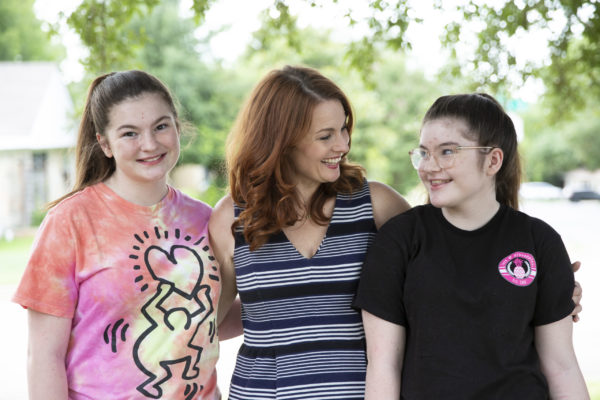 A smiling woman standing with her arms around her two daughters.
