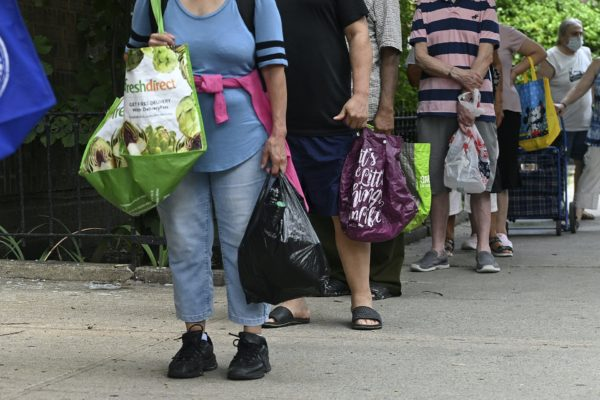 People wait in line with grocery bags.