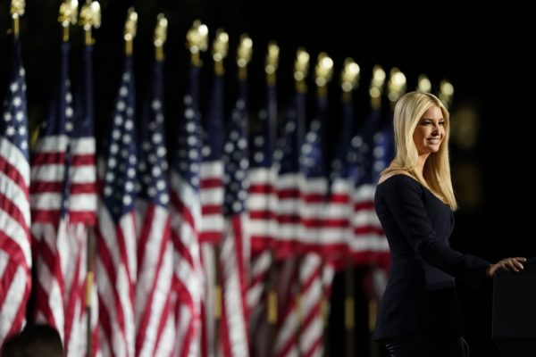 Ivanka Trump giving a speech in front of a row of American flags.