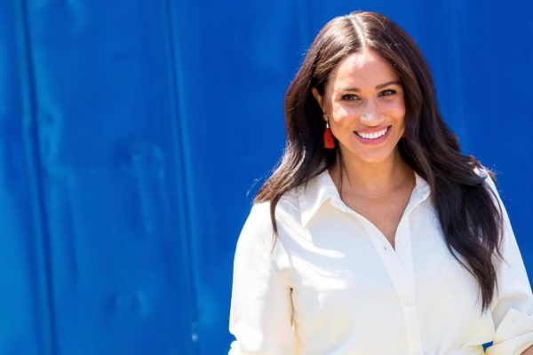 Meghan Markle smiles at camera against a blue background.