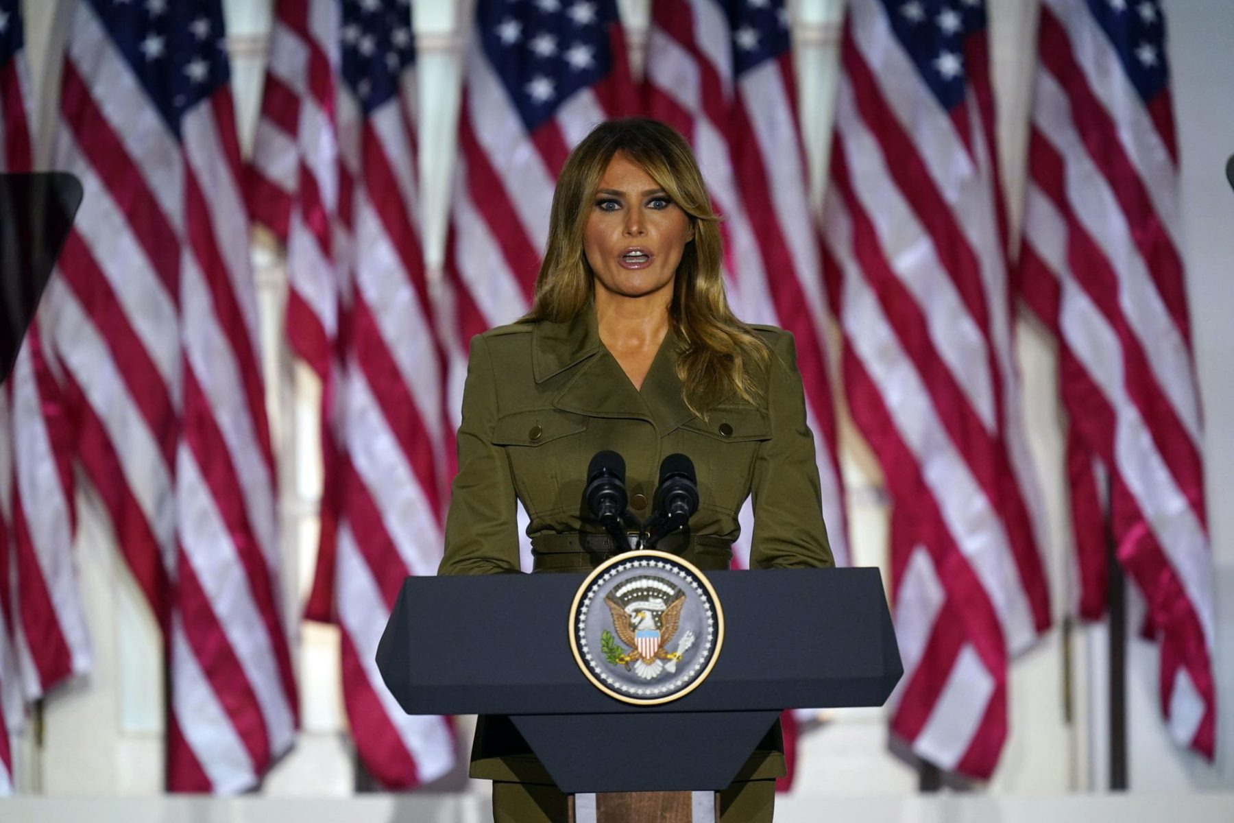 Melania Trump standing in front of a row of American flags.