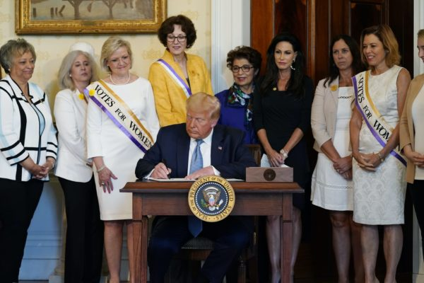 President Donald Trump signs a document surrounded by women surrogates.