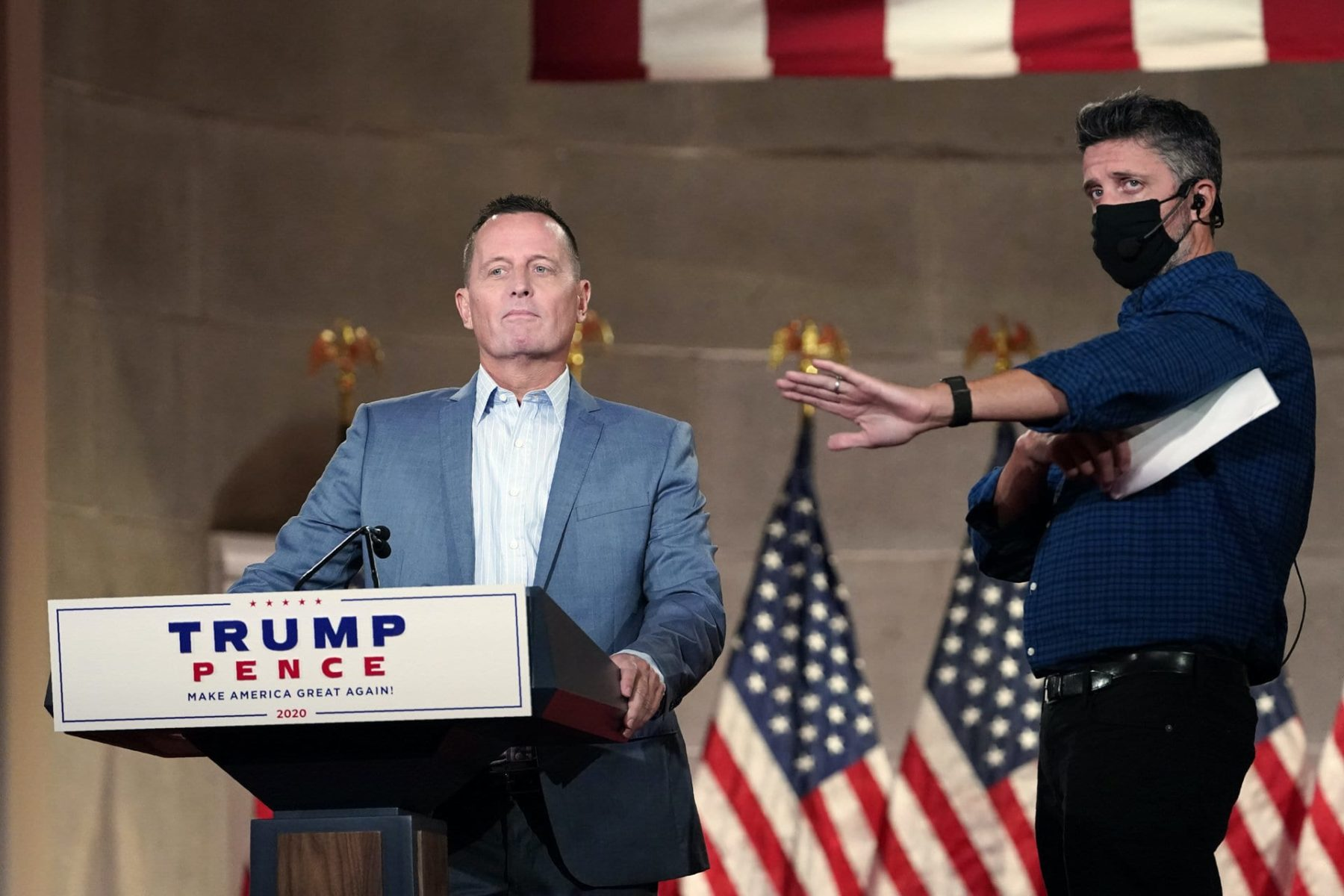 Richard Grenell stands at a Trump-Pence podium.
