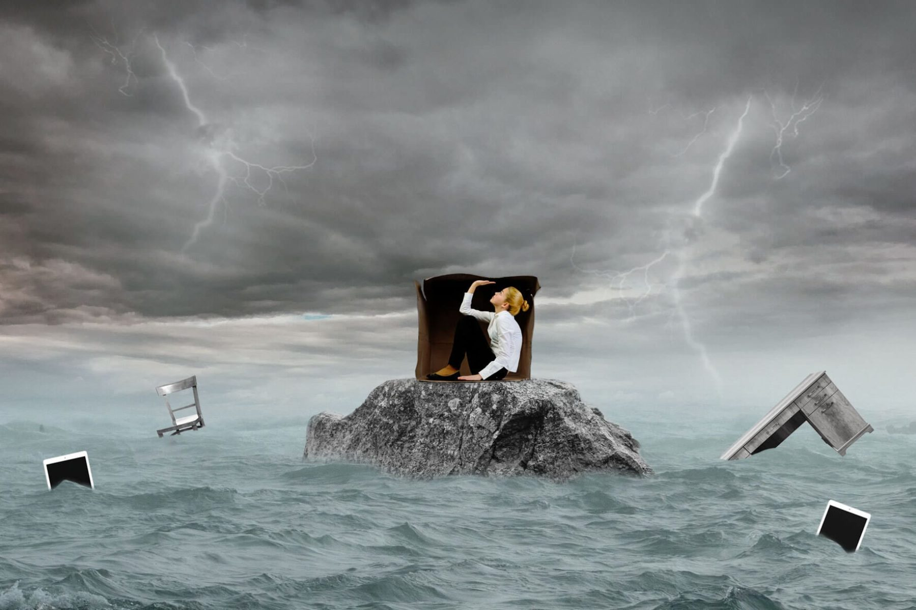 A composite illustration of a woman trapped in a box with stormy seas surrounding her.