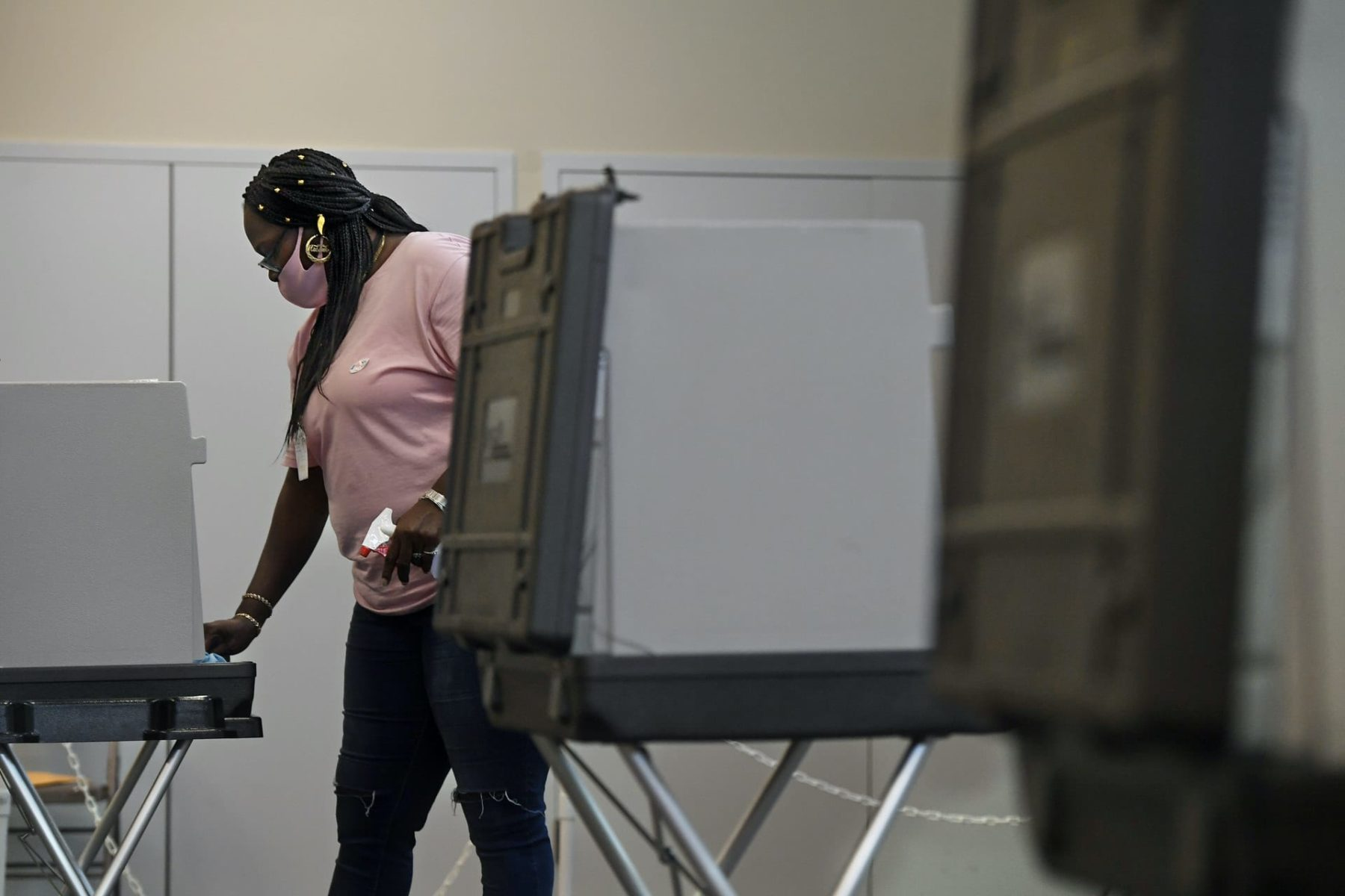 A woman cleans a voting booth.