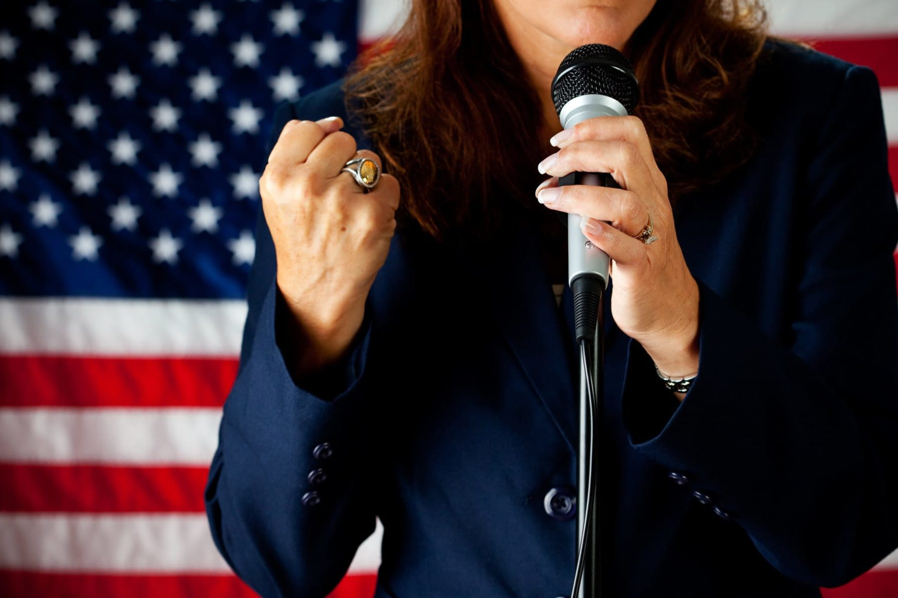 A woman candidate standing in front of an American flag.