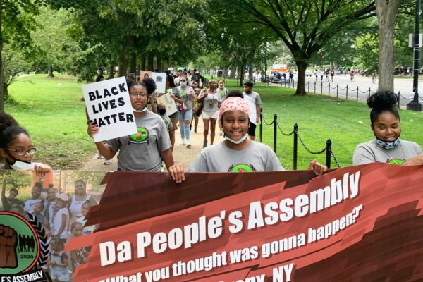 A group of children and parents from the Bronx, holding a banner that reads Da People's Assemblage, attending the 2020 March on Washington to protest.