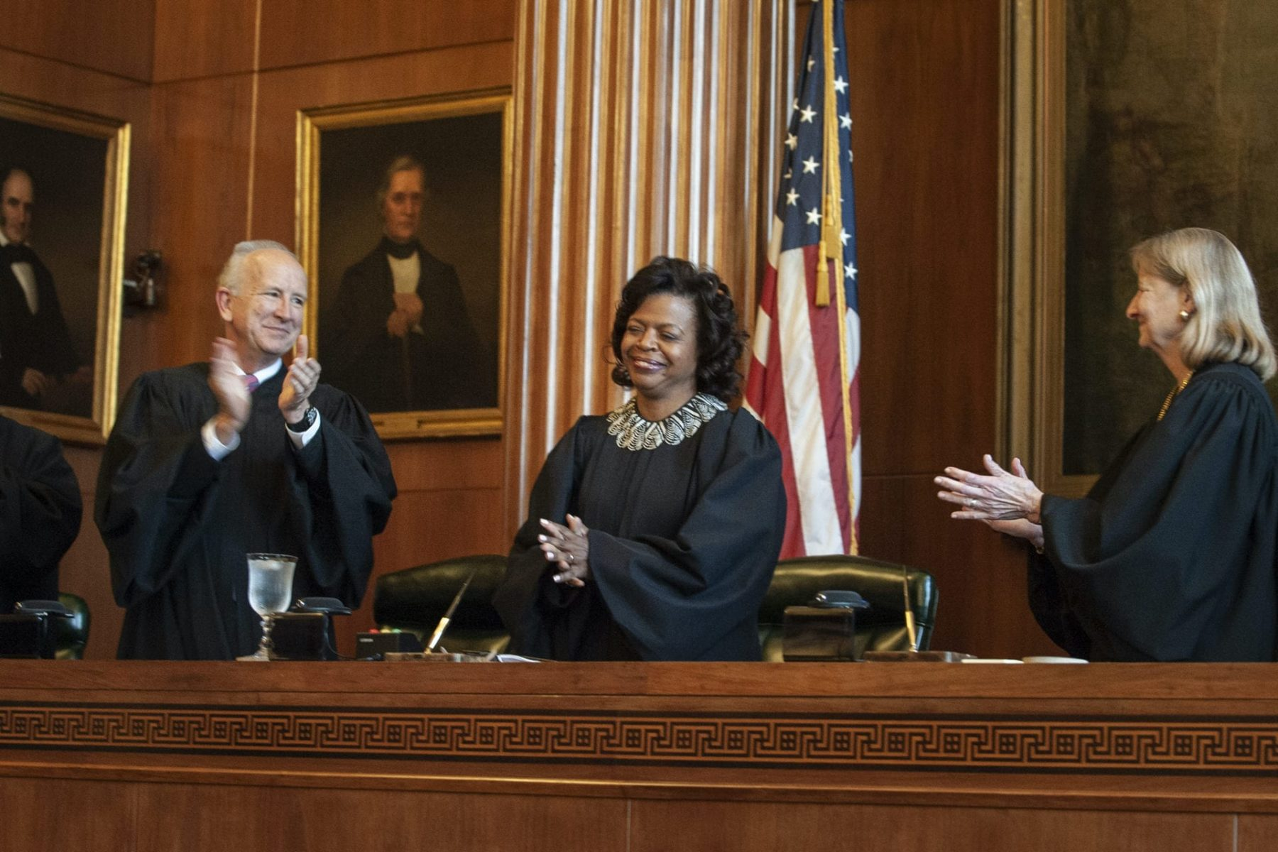 """In this March 7, 2019 file photo, Associate Justices Paul Newby and Robin Hudson applaud for new Chief Justice Cheri Beasley, center, of the N.C. Supreme Court during Beasley's investiture ceremony in Raleigh. In North Carolina's Supreme Court chamber, above the seat held by Beasley, the second African American chief justice, hangs a towering painting of Chief Justice Thomas Ruffin, a 19th century slave owner and jurist who authored a notorious opinion about the """"absolute"""" rights of slaveholders over the enslaved.In October 2018 the state Supreme Court named a commission to review the portraits in the building that houses the court ,including Ruffin's. (Paul Woolverton/The Fayetteville Observer via AP)"""