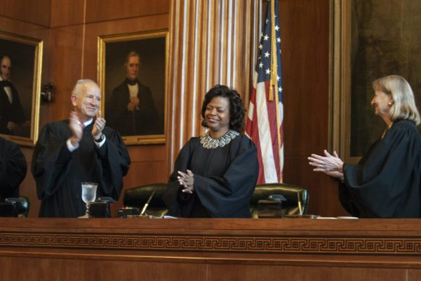 "In this March 7, 2019 file photo, Associate Justices Paul Newby and Robin Hudson applaud for new Chief Justice Cheri Beasley, center, of the N.C. Supreme Court during Beasley's investiture ceremony in Raleigh. In North Carolina's Supreme Court chamber, above the seat held by Beasley, the second African American chief justice, hangs a towering painting of Chief Justice Thomas Ruffin, a 19th century slave owner and jurist who authored a notorious opinion about the ""absolute"" rights of slaveholders over the enslaved. In October 2018 the state Supreme Court named a commission to review the portraits in the building that houses the court ,including Ruffin's.  (Paul Woolverton/The Fayetteville Observer via AP)"