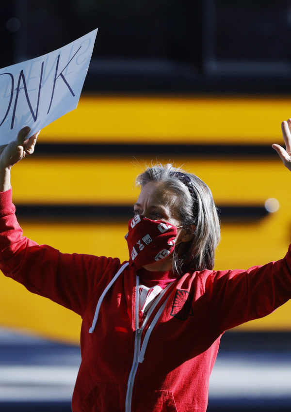 Lara Center, dressed in a red hoodie and holding a sign that says HONK in all caps above her head, protests in Denver to protect public schools from budget cuts.