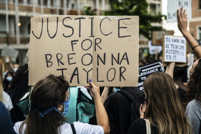 A girl holding a cardboard sign asking justice for Breonna Taylor demonstrating in Mestre, Venice, Italy on June 6, 2020, to protest the killing of George Floyd by a policeman in the USA.