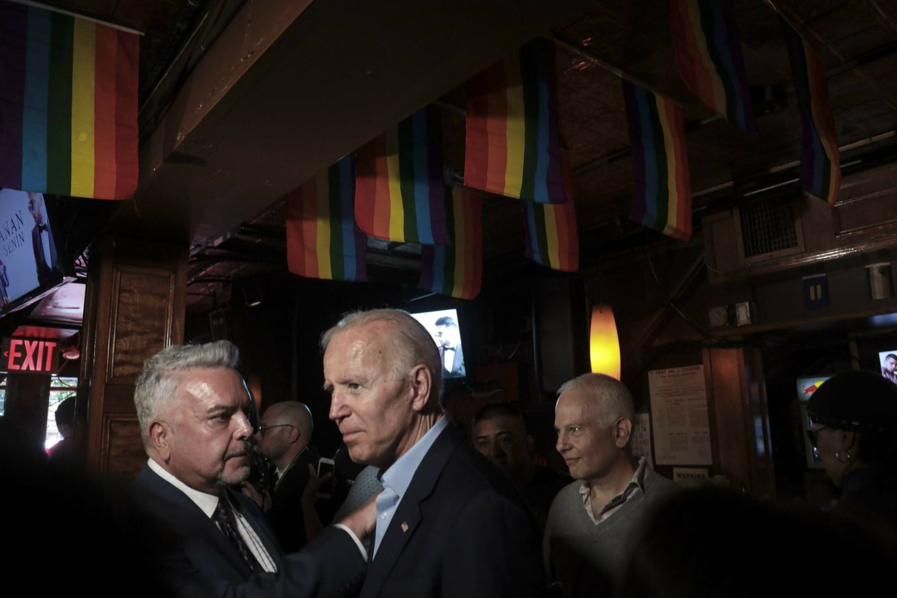 Joe Biden at the Stonewall Inn standing under LGBTQ flags.
