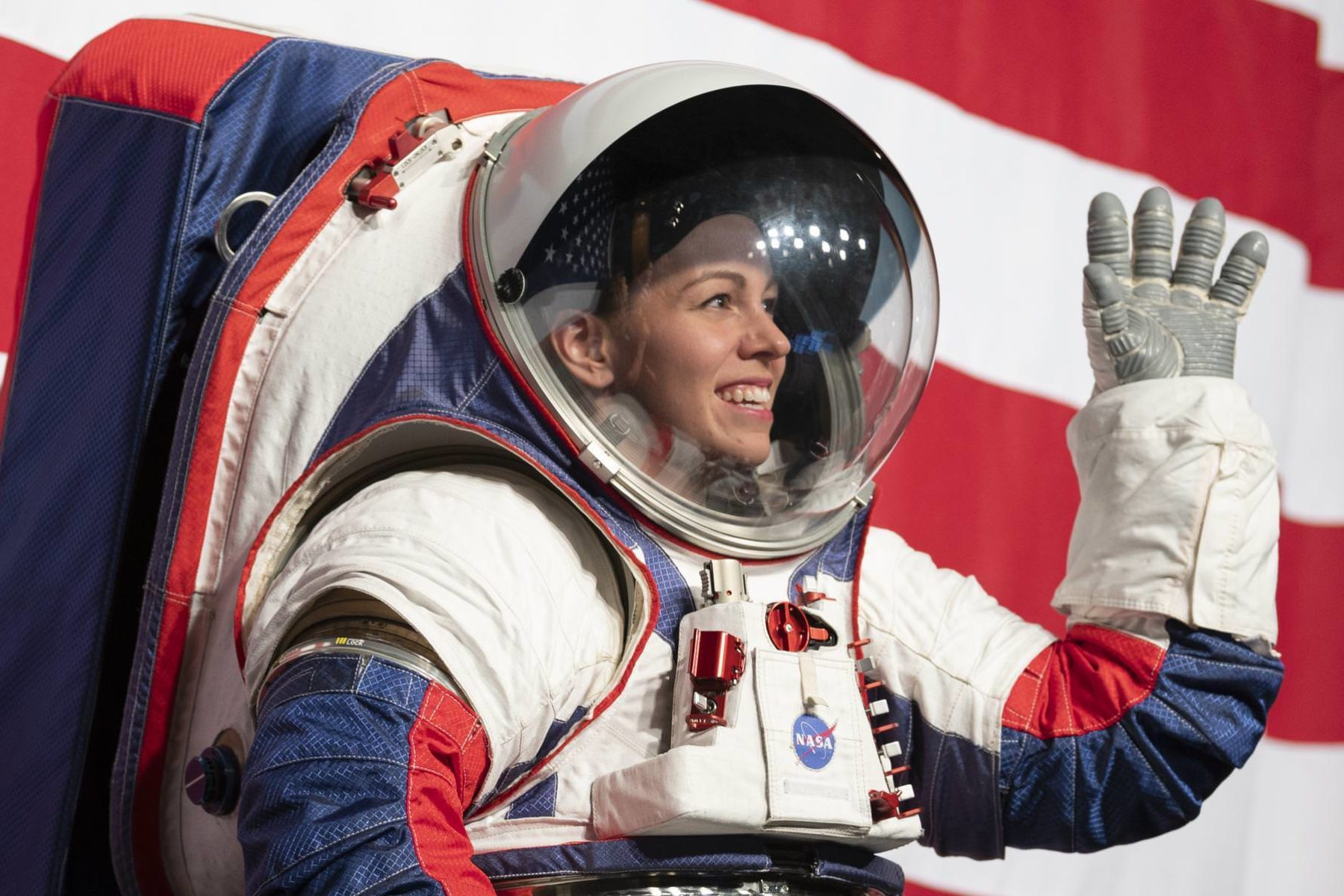 Kristine Davis, a spacesuit engineer at NASA's Johnson Space Center, wearing a ground prototype of NASA's new Exploration Extravehicular Mobility Unit (xEMU), pictured here waving and smiling during a demonstration of the suit, Tuesday, Oct. 15, 2019 at NASA Headquarters in Washington.