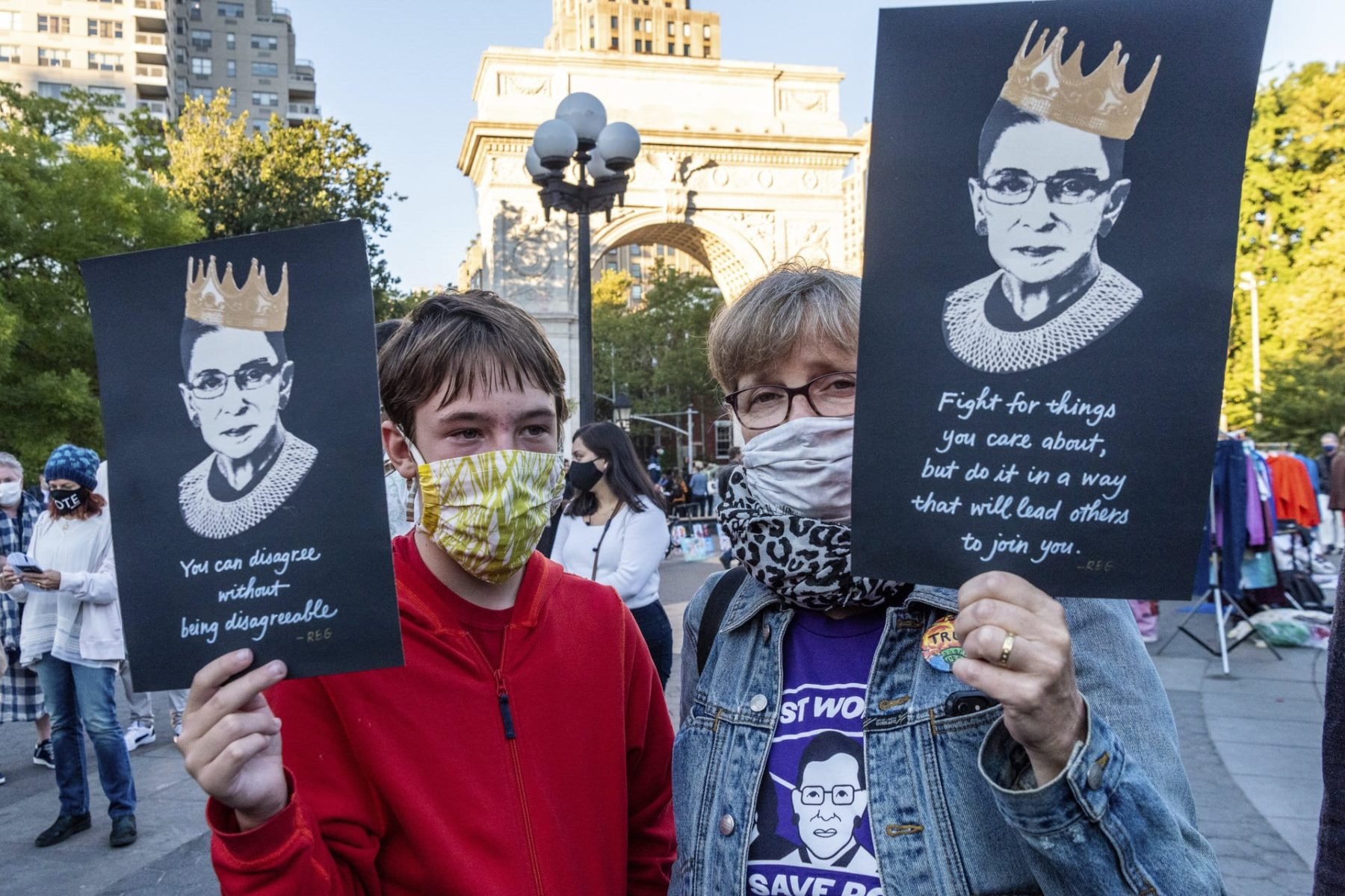 Two people carrying signs with Ruth Bader Ginsburg's face on them.
