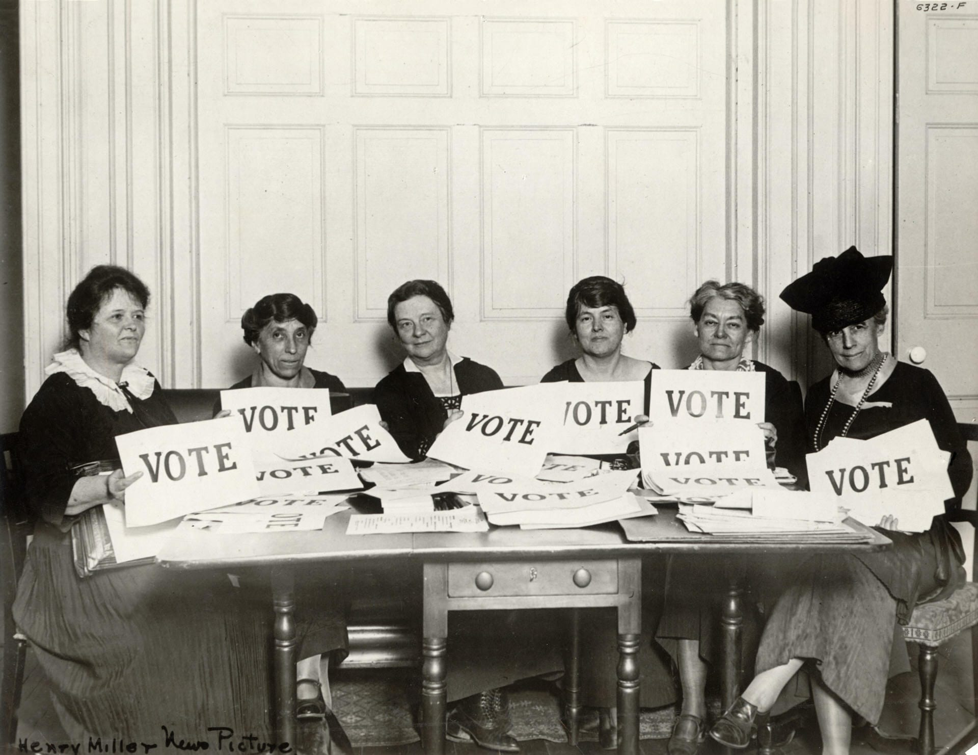 "A group of women in a black and white photo hold signs that say ""vote."""