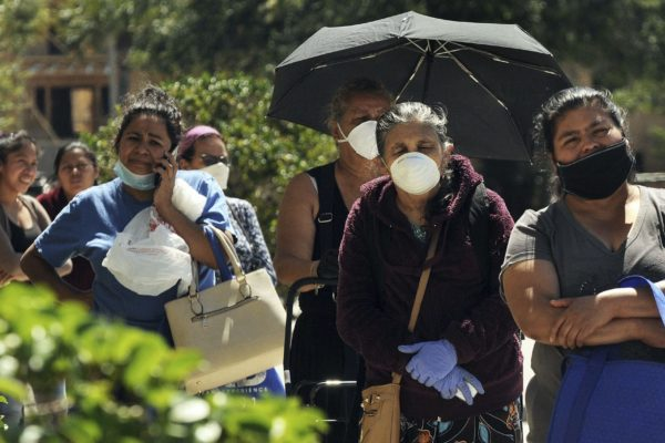 Women wearing protective masks wait in a queue to receive food assistance provided by the Second Harvest Food Bank of Central Florida at a food distribution event staffed by volunteers at the Calvario City Church. Food banks across the United States are being overwhelmed due to the thousands of people who have lost their jobs due to the coronavirus (COVID-19) pandemic.