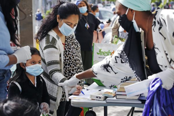 Volunteer Sequaña Williams-Hechavarria, right, instructs youngster Jade Suarez to look beneath the table for books as Jade's mother, Maria, signs up for assistance and free supplies provided by Sistas Van during the coronavirus outbreak at a busy Bushwick intersection in the Brooklyn borough of New York, Tuesday, May 19, 2020. Sistas Van was originally launched by the nonprofit Black Women's Blueprint to help survivors of sexual and reproductive violence and physical abuse. But during the coronavirus, the women's network has pivoted to delivering badly-needed resources to black and Hispanic communities, which have had some of the city's highest rates of contagion and death toll of the fast-spreading virus.
