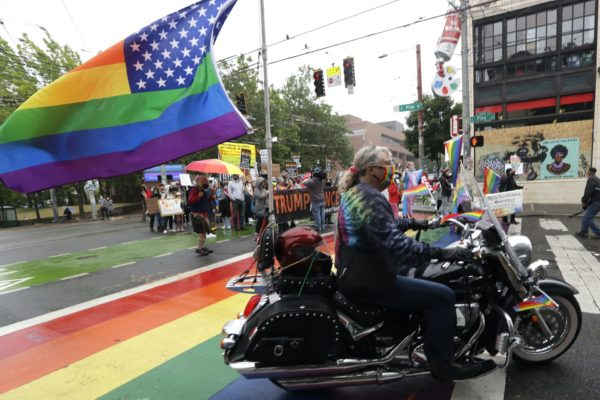 A person on a motorcycle with a rainbow flag attached to the back drives by protesters with a Trump-Pence sign.