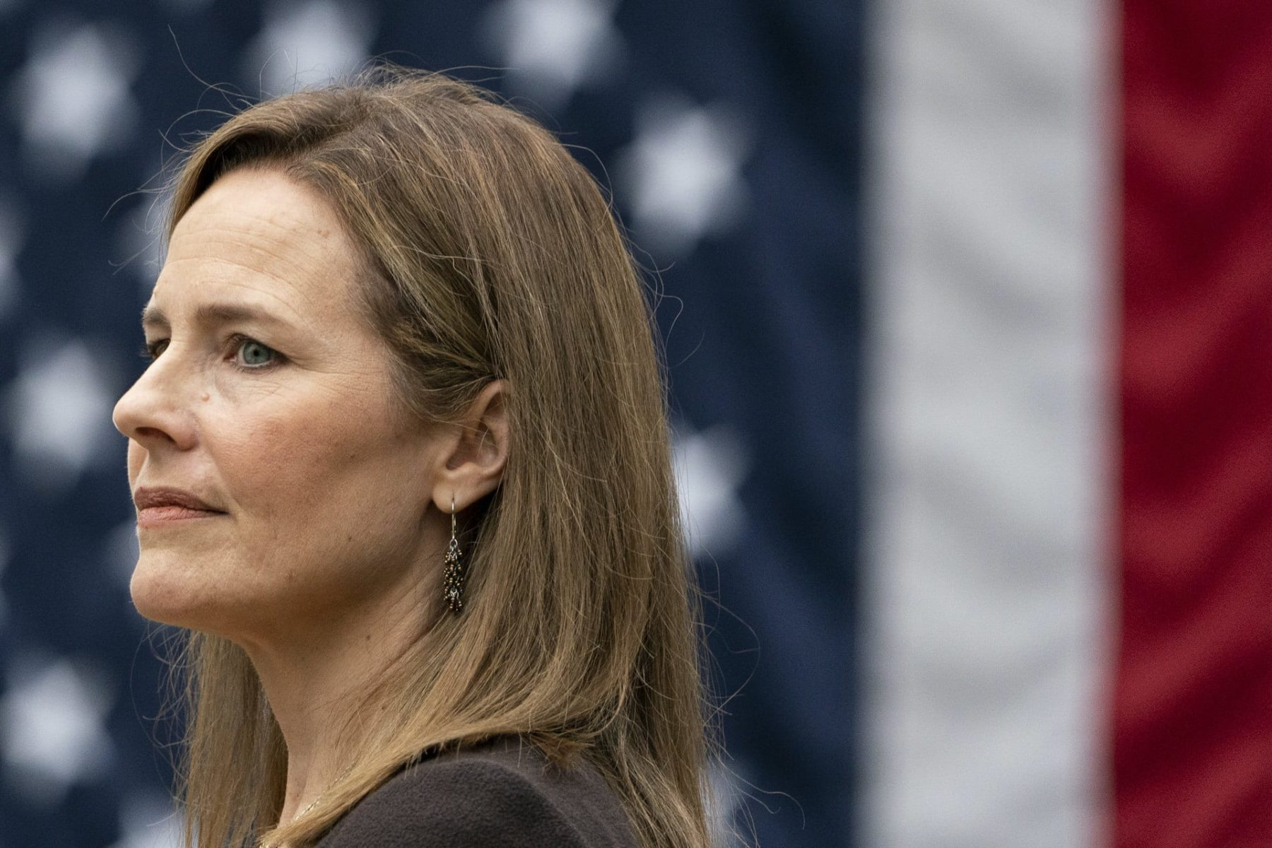 Amy Coney Barrett stands in front of the American flag.