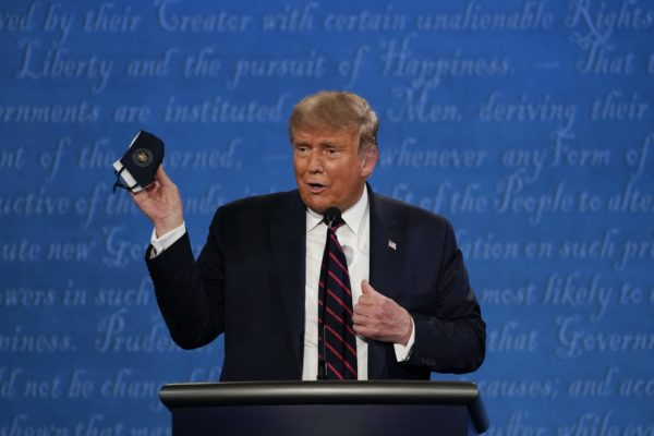 In this Sept. 29, 2020, file photo, President Donald Trump holds up his facemask during the first presidential debate at Case Western University and Cleveland Clinic, in Cleveland, Ohio. President Trump and first lady Melania Trump have tested positive for the coronavirus, the president tweeted early Friday. In this (AP Photo/Julio Cortez, File)