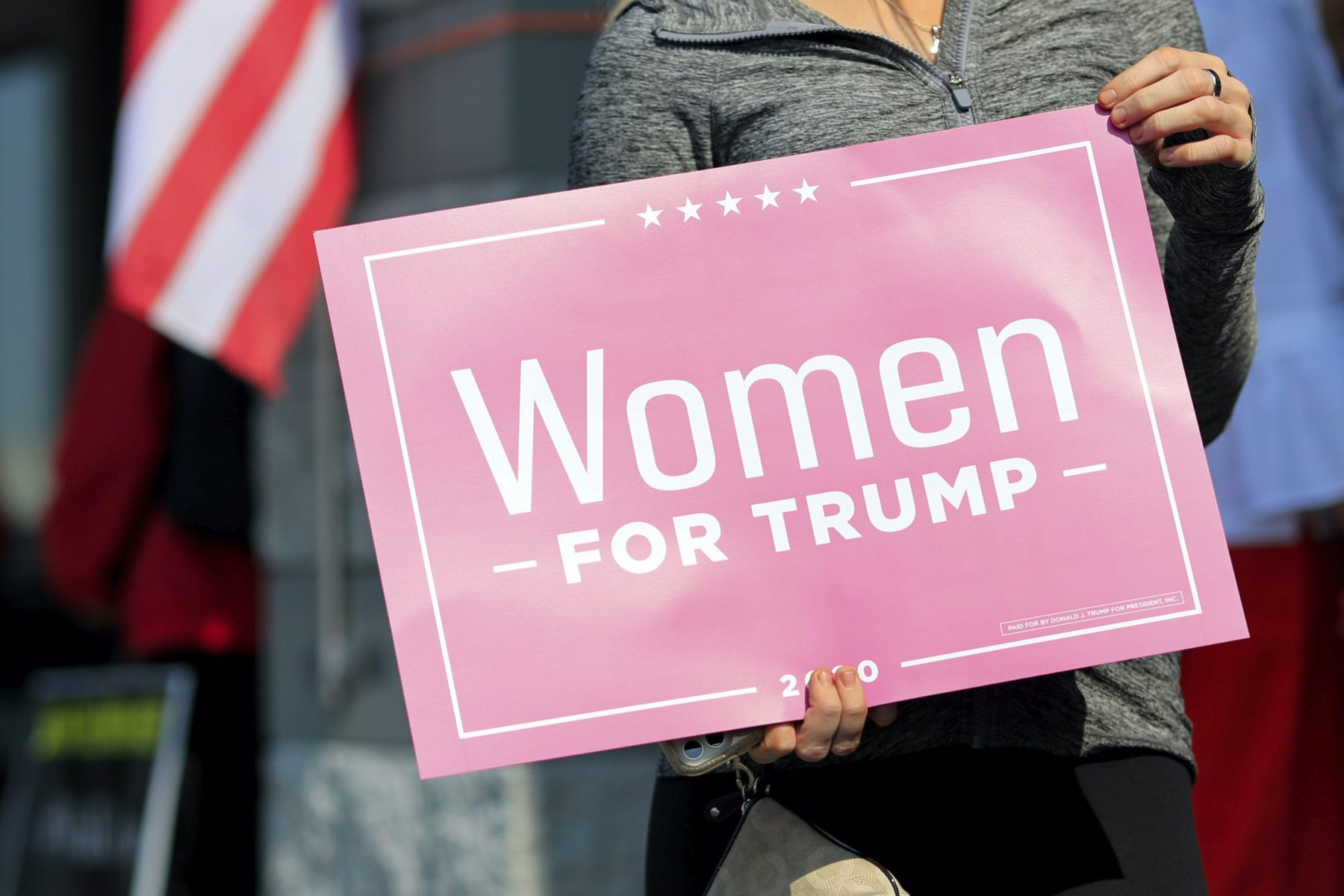 A voter holds a sign in support of Women For Trump outside the Hamilton County Board of Elections as people arrive to participate in early voting, Tuesday, Oct. 6, 2020, in Norwood, Ohio.