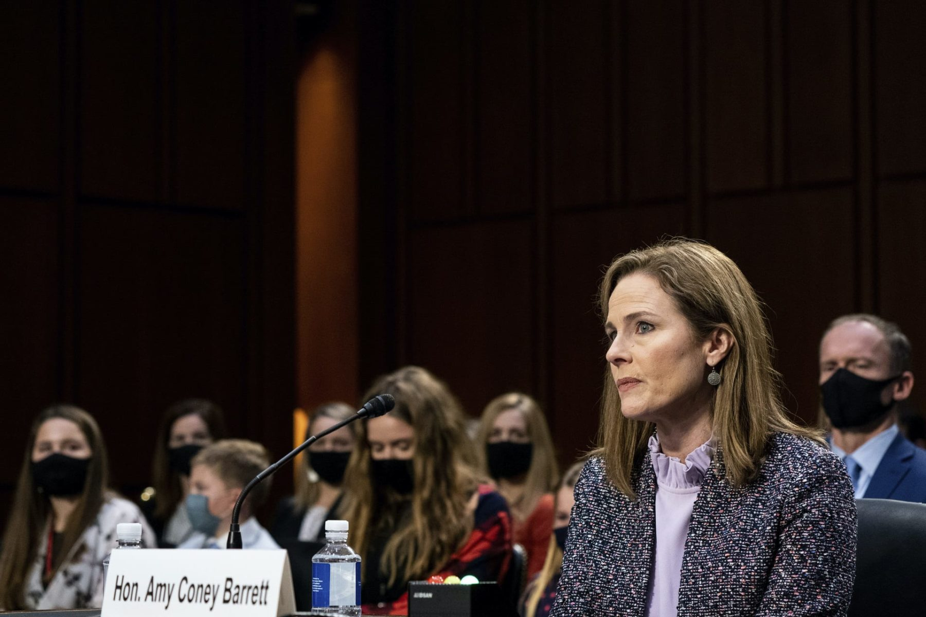 Amy Coney Barrett sits at a desk in front of the Senate Judiciary Committee.