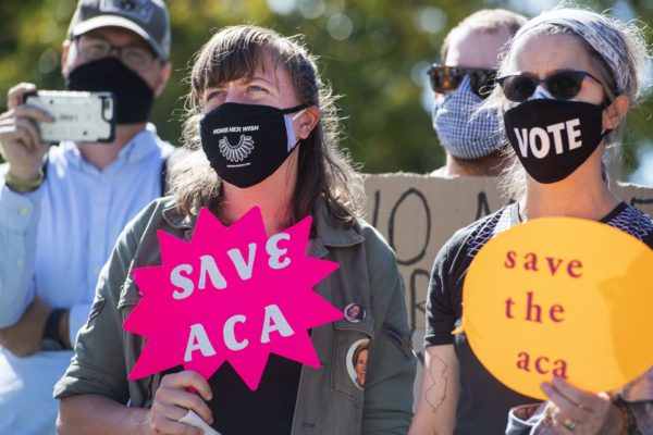 Protesters hold signs about the Affordable Care Act.