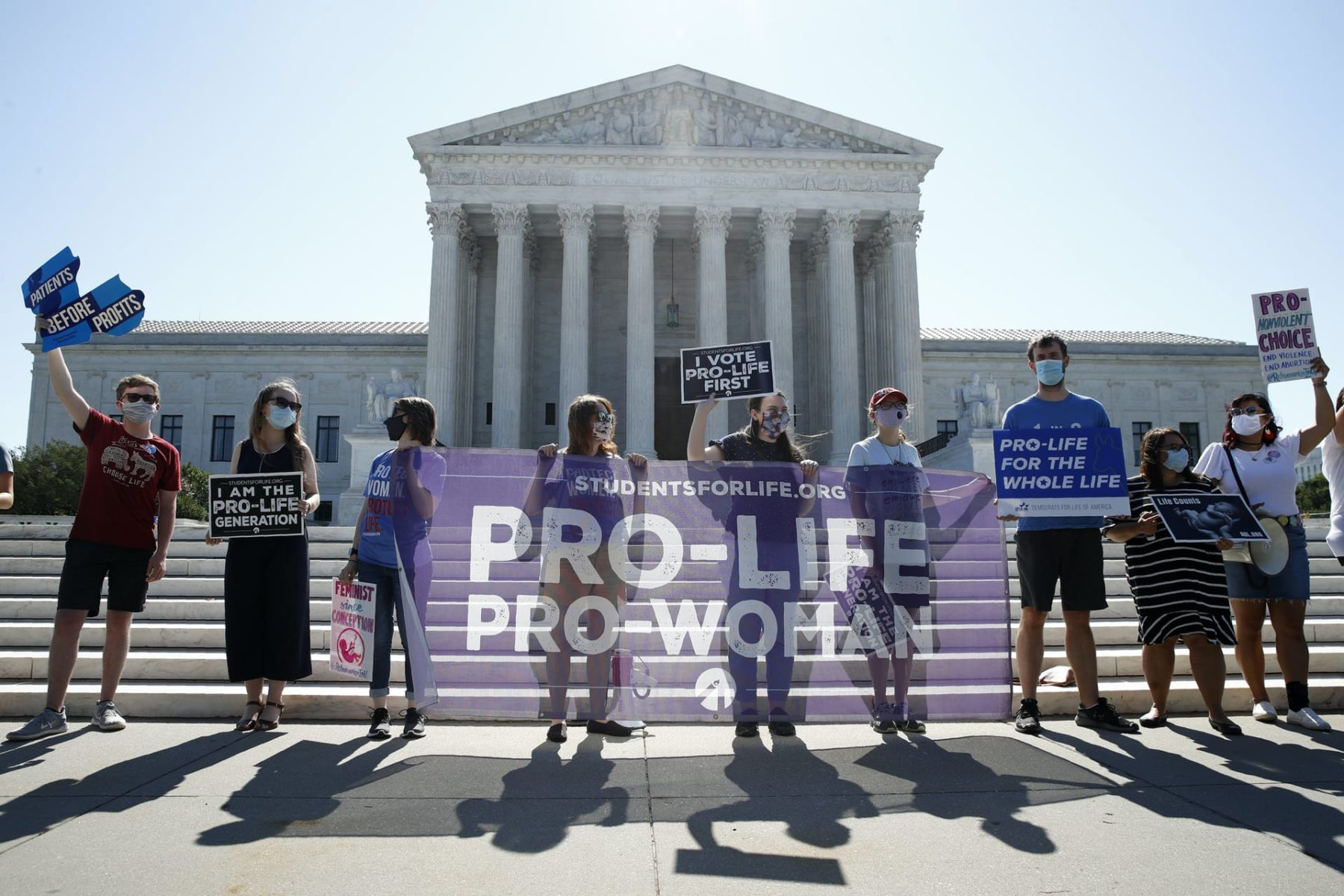 A group stands in front of the Supreme Court with a sign that reads,