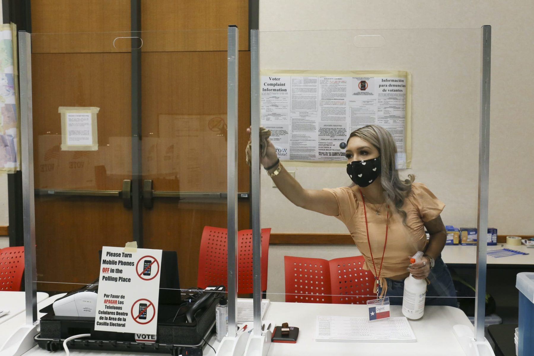 A poll worker cleans a plexiglass barrier at a Texas polling place.