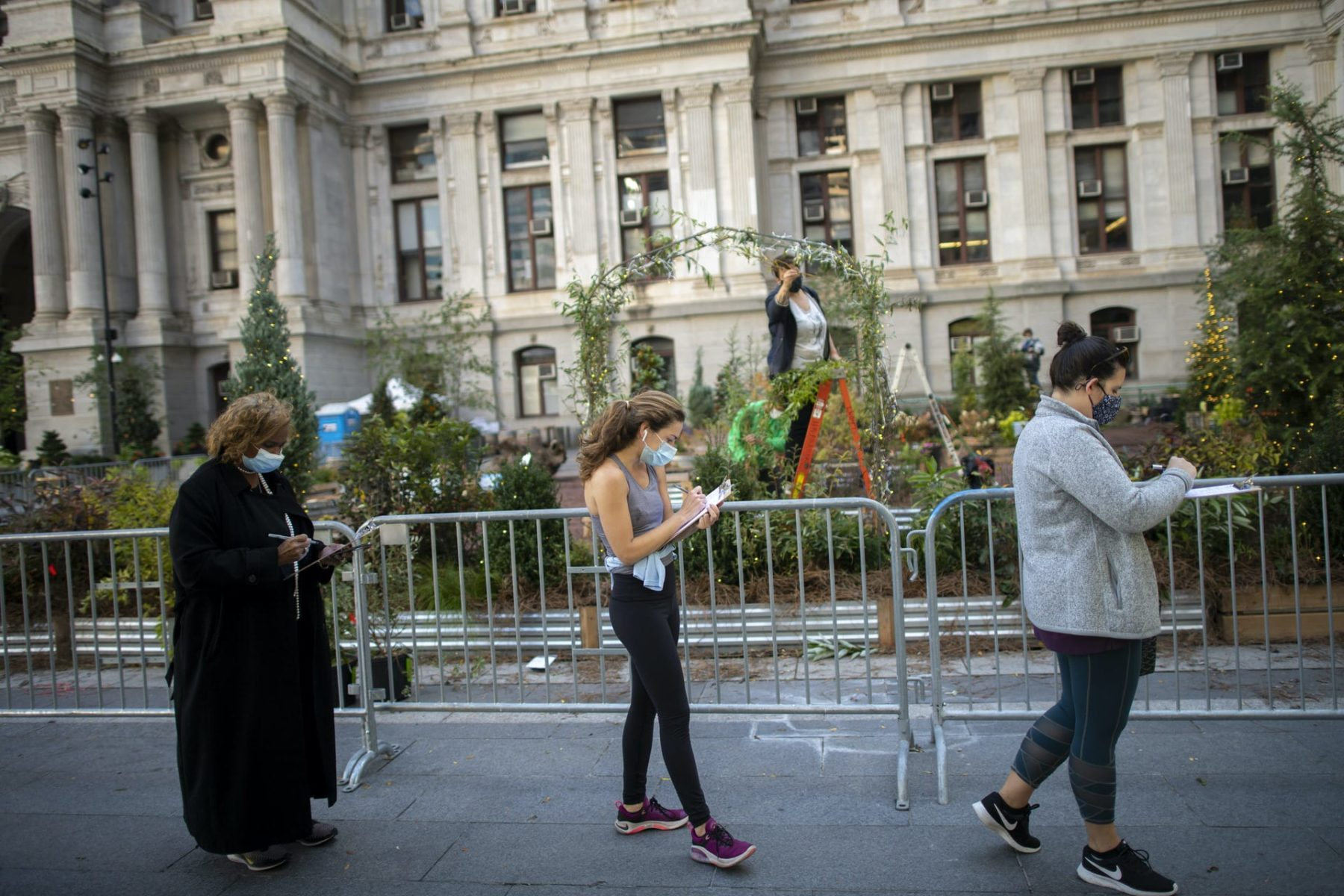 Voters in Philadelphia complete registration paperwork while waiting outside of Philadelphia City Hall for early voting on October 27, 2020.