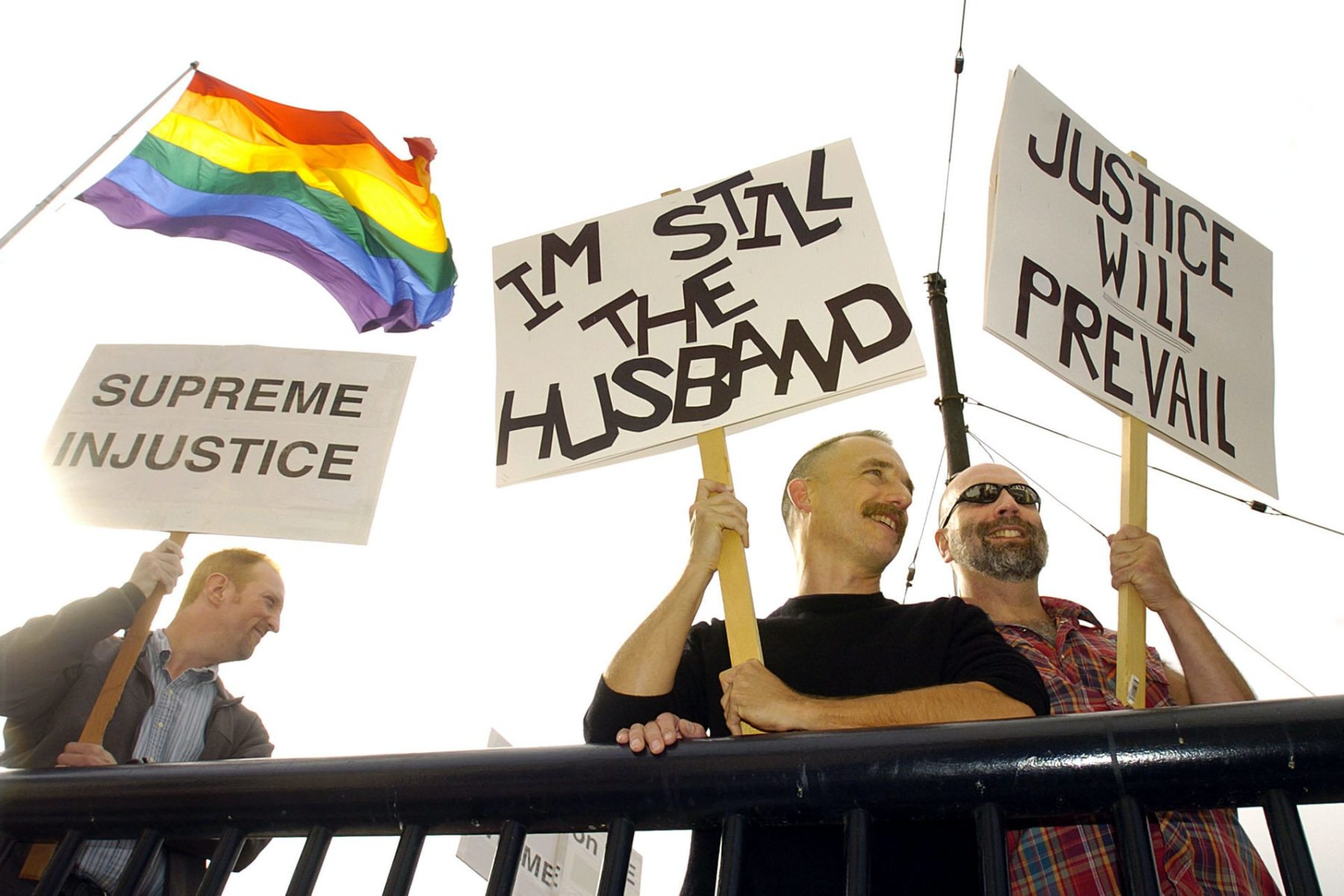 Three people stand with signs supporting marriage equality as the LGBTQ flag waves in the background.