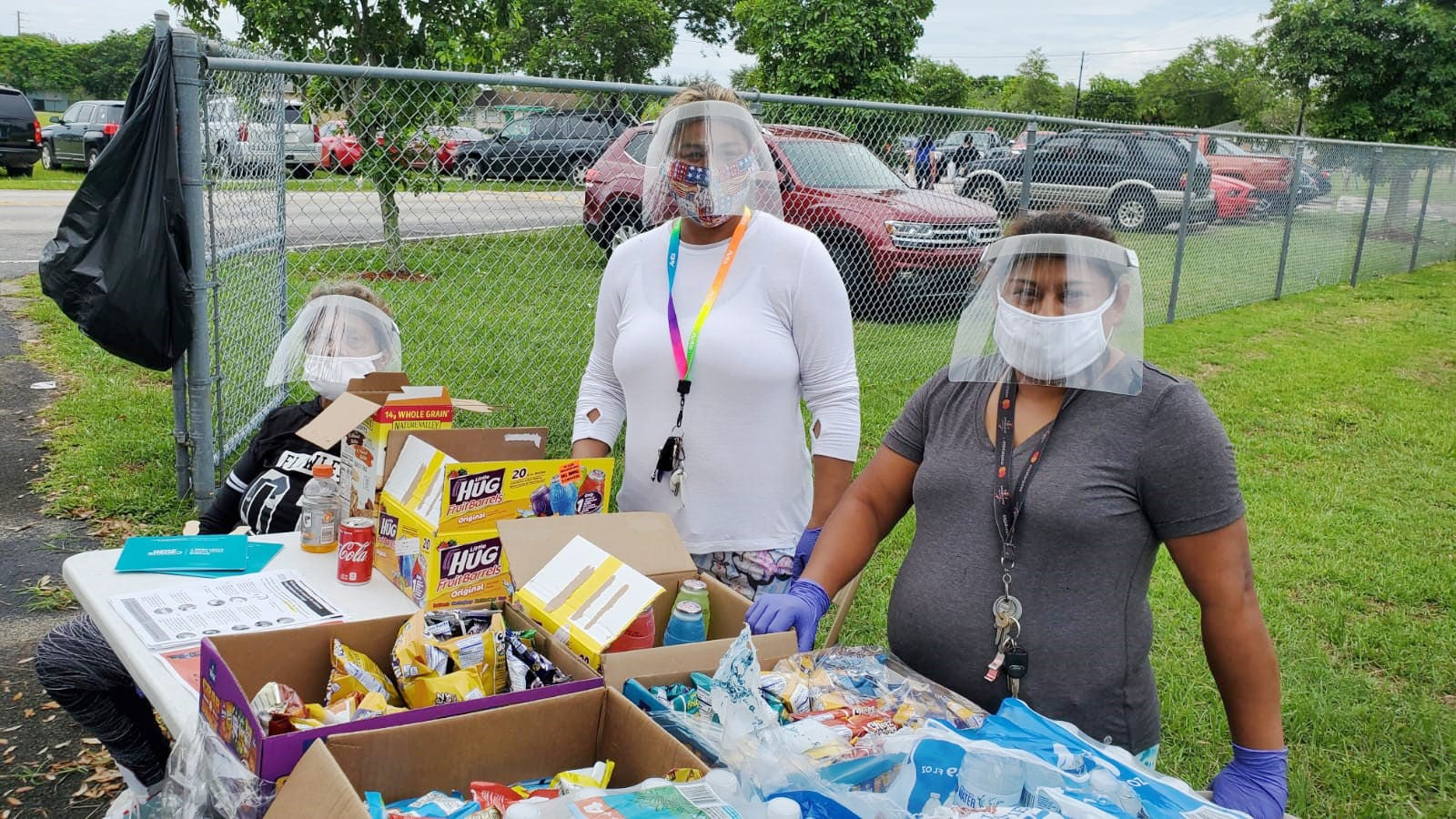 Three women wearing face shields passing out food.