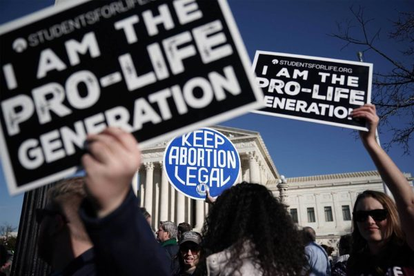 Protesters carry anti-abortion signs and abortion access signs.