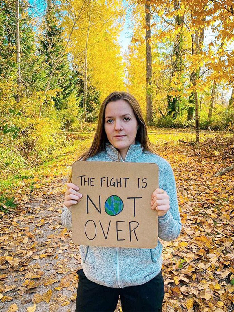 "A woman stands in a forest with a sign that reads, ""The fight is not over."""