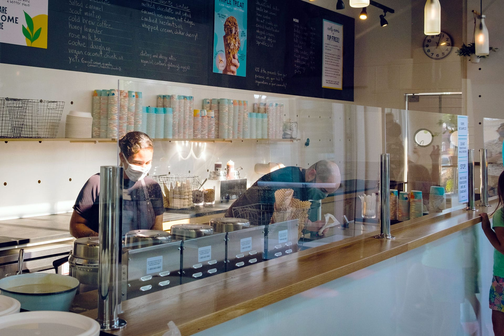 Two workers behind the counter at an ice cream shop.