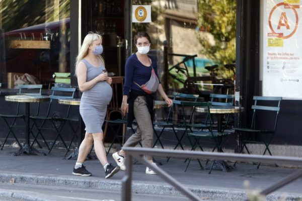 Two pregnant women wearing masks walk down the street.