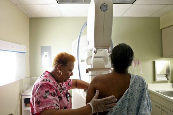 A woman administers a mammogram to another woman.