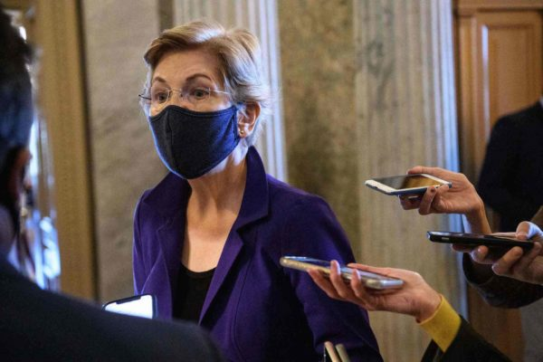 Sen. Elizabeth Warren surrounded by reporters holding phones to record.