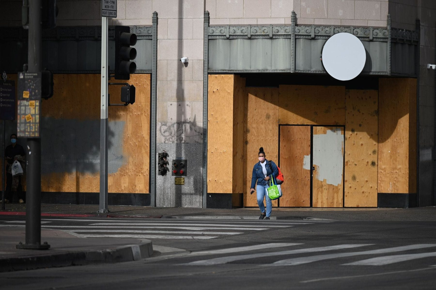 A woman wearing a facemask to prevent the spread of coronavirus walks past a boarded up storefront at the intersection of Hill Street and 5th Street in downtown Los Angeles, California, November 5, 2020 as the country awaits the result of the November 3 US presidential election. - Businesses in major US cities were boarded up in anticipation of unrest. The nail-biting US election was on the cusp of finally producing a winner Thursday, with Democrat Joe Biden declaring