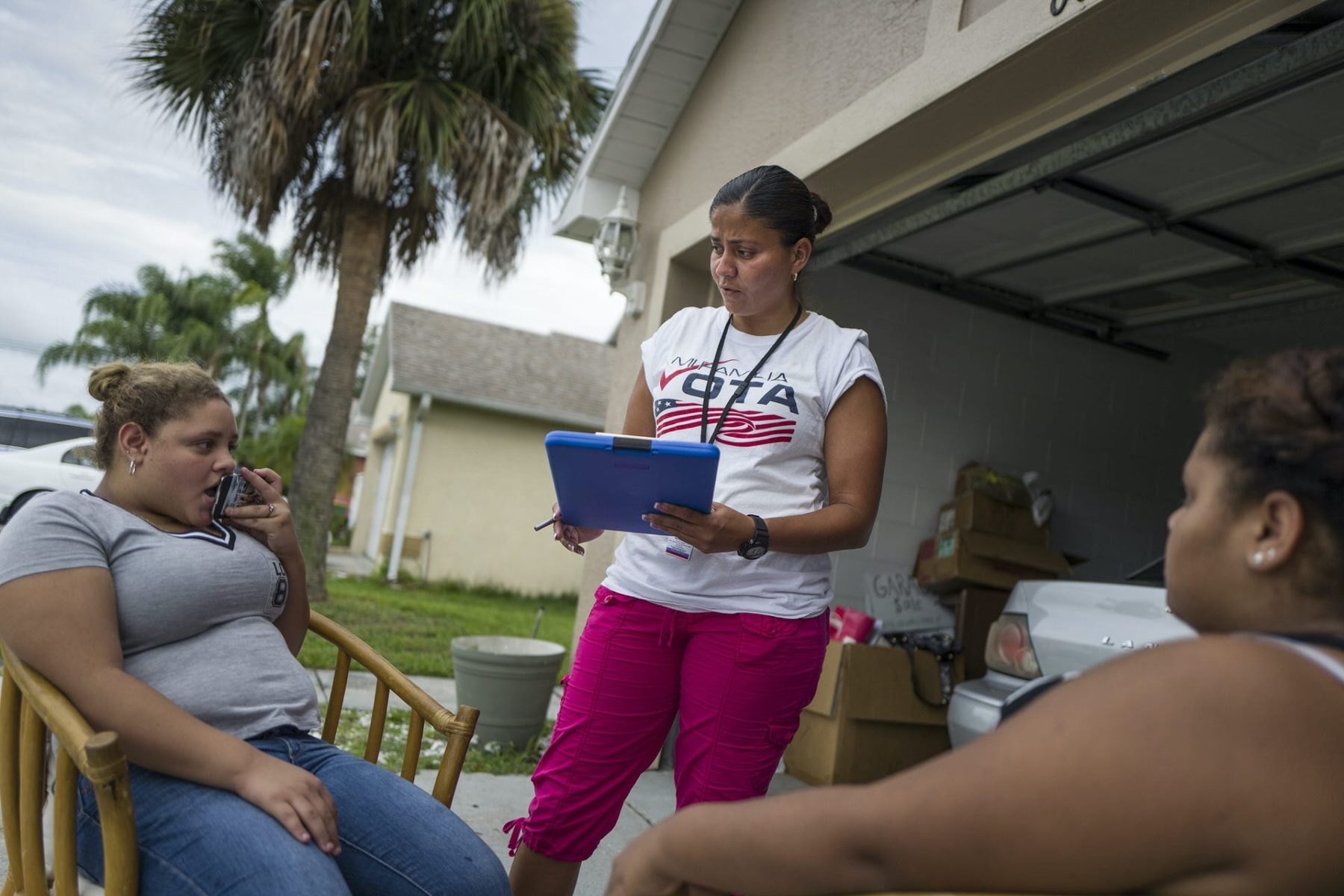 Soraya Marquez, the state coordinator for Mi Familia Vota and her crew hit a Puerto Rican neighborhood trying to get Latinos to register to vote in the 2016 presidential election on July 24, 2015 in Kissimmee, FL. Jeamy Ramirez gets a young girl (18) to register to vote in a Puerto Rican neighborhood in Kissimmee. (Photos by Charles Ommanney/The Washington Post via Getty Images)