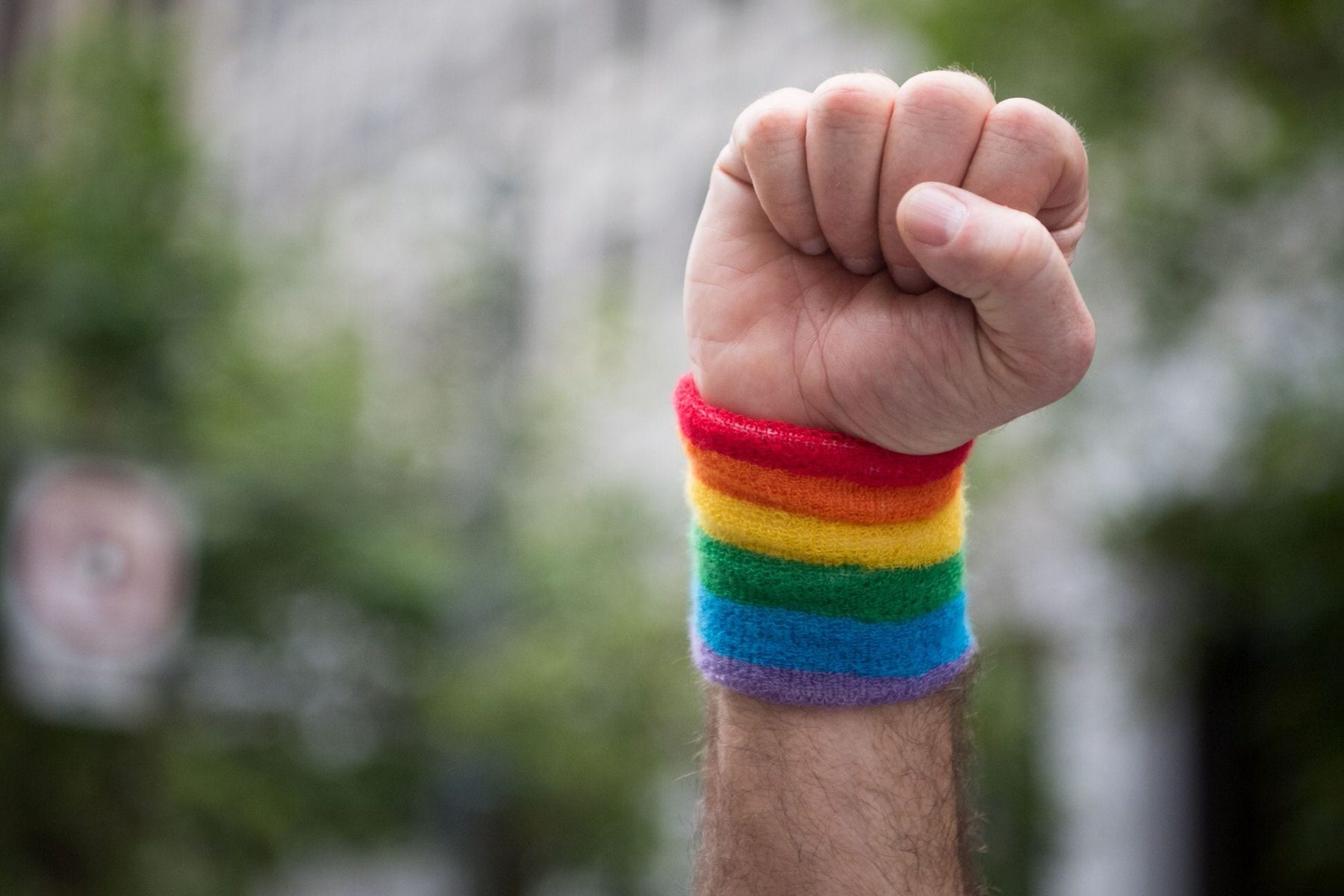 A fist raised in the air with a rainbow cuff.