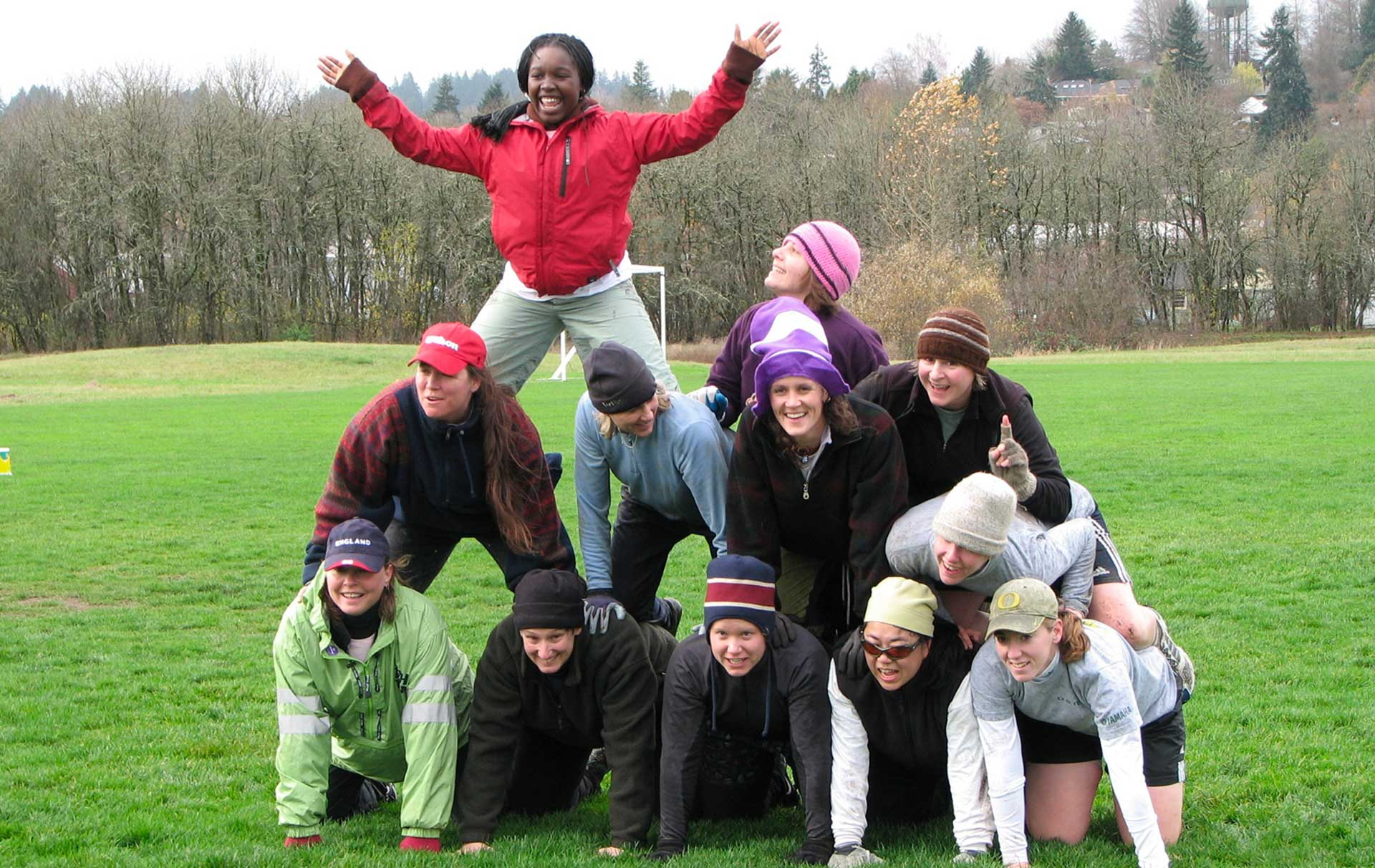A group posing in a pyramid on a football field.
