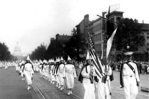 A line of women marching in a KKK parade.