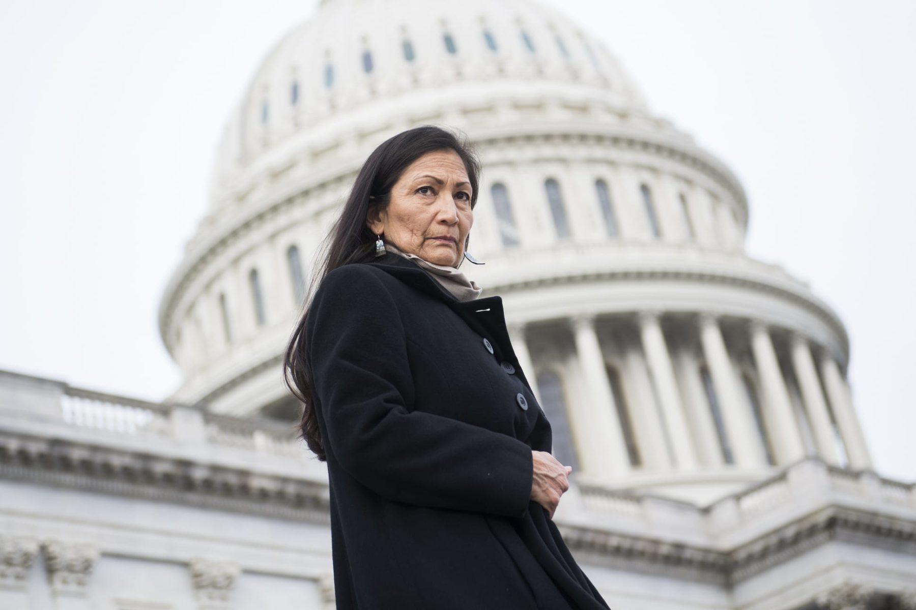 DEb Haaland standing in front of the U.S. Capitol building.