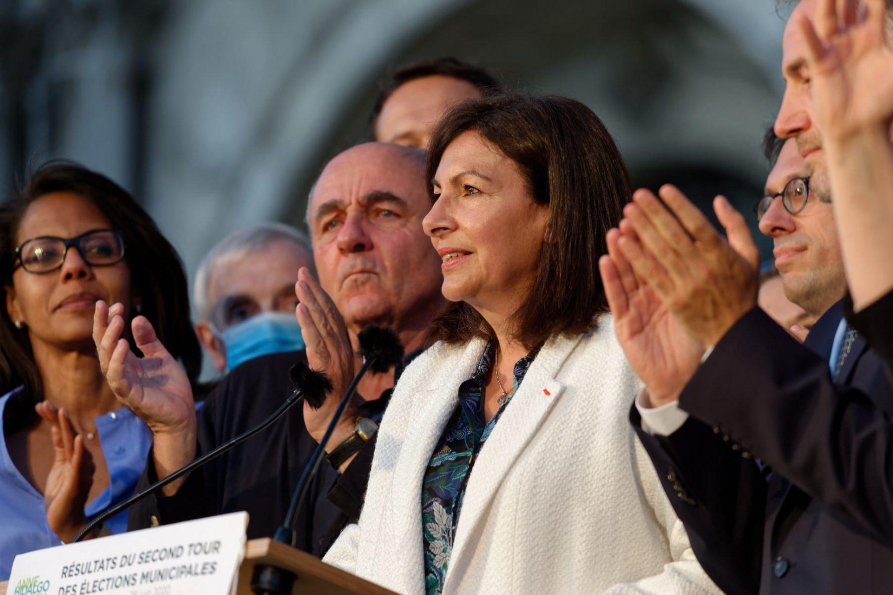 Paris Mayor Anne Hidalgo stands at a podium.